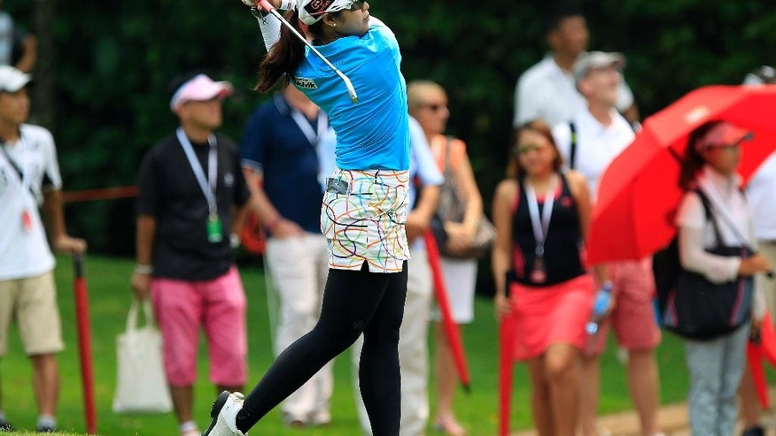 Pornanong Phatlum of Thailand hits a shot on the 18th hole during the third round of the LPGA Malaysia golf tournament at Kuala Lumpur Golf and Country Club in Kuala Lumpur, Malaysia, Saturday, Oct. 11, 2014. (AP Photo/Lai Seng Sin)