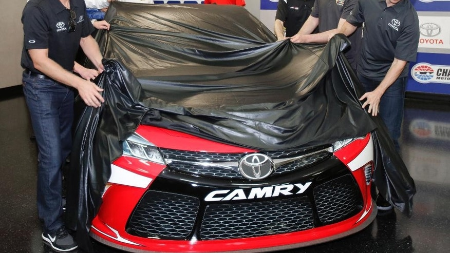 Drivers Clint Bowyer, left, Denny Hamlin, right, Kyle Busch, second from right, and Matt Kenseth, third from right, unveil a new 2015 Toyota Camry race car during a news conference before the NASCAR Sprint Cup series Bank of America 500 auto race at Charlotte Motor Speedway in Concord, N.C., Saturday, Oct. 11, 2014. (AP Photo/Terry Renna)