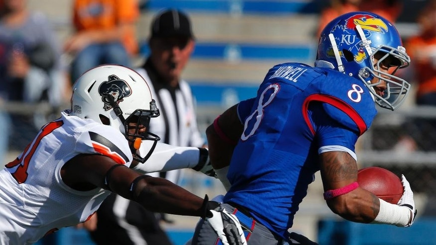 Kansas wide receiver Nick Harwell (8) is tackled by Oklahoma State safety Tre Flowers (31) during the first half of an NCAA college football game in Lawrence, Kan., Saturday, Oct. 11, 2014. (AP Photo/Orlin Wagner)