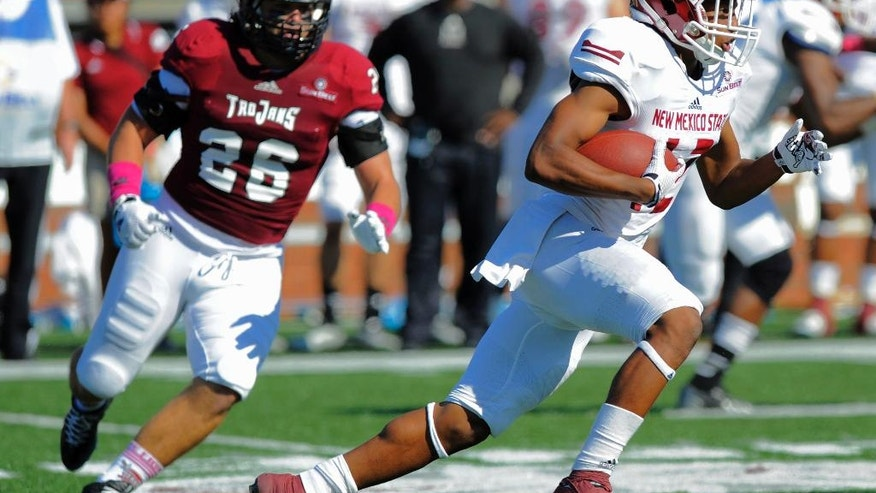 New Mexico State running back Larry Rose III (12) gets by Troy University linebacker Mitchell Roland (26) in the first half during an NCAA college football game in Troy, Ala., on Saturday, Oct. 11, 2014. (AP Photo/The Montgomery Advertiser, Mickey Welsh)