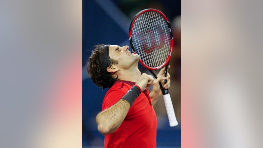 Roger Federer of Switzerland reacts after defeating Gilles Simon of France in the final match of the Shanghai Masters tennis tournament in Shanghai, China, Sunday, Oct. 12, 2014. Federer captured his fourth title of the year at the Shanghai Masters on Sunday. (AP Photo/Vincent Thian)
