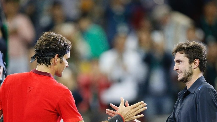 Roger Federer of Switzerland, left, and Gilles Simon of France greet after Federer won the men's singles final at the Shanghai Masters Tennis Tournament in Shanghai, China, Sunday, Oct. 12, 2014.  (AP Photo/Vincent Thian)