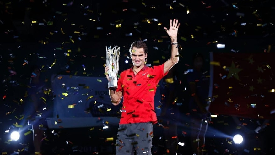 Roger Federer of Switzerland holds the trophy during awards ceremony after the men's singles final against Gilles Simon of France at the Shanghai Masters Tennis Tournament in Shanghai, China, Sunday, Oct. 12, 2014.  (AP Photo/Vincent Thian)