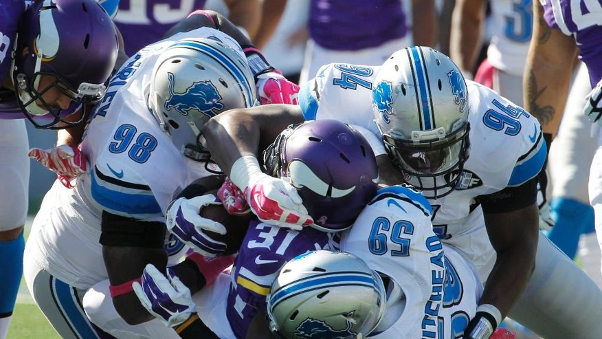 Minnesota Vikings running back Jerick McKinnon (31) is stopped by Detroit Lions defensive tackle Nick Fairley (98), outside linebacker Tahir Whitehead (59) and defensive end Ezekiel Ansah (94) during the first half of an NFL football game Sunday, Oct. 12, 2014, in Minneapolis. (AP Photo/Ann Heisenfelt)
