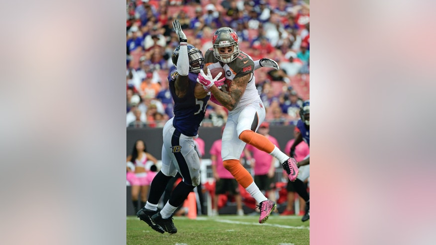 Tampa Bay Buccaneers wide receiver Mike Evans (13) catches a 17-yard touchdown pass in front of Baltimore Ravens inside linebacker C.J. Mosley, left, during the second half of an NFL football game in Tampa, Fla., Sunday, Oct. 12, 2014. (AP Photo/Phelan M. Ebenhack)