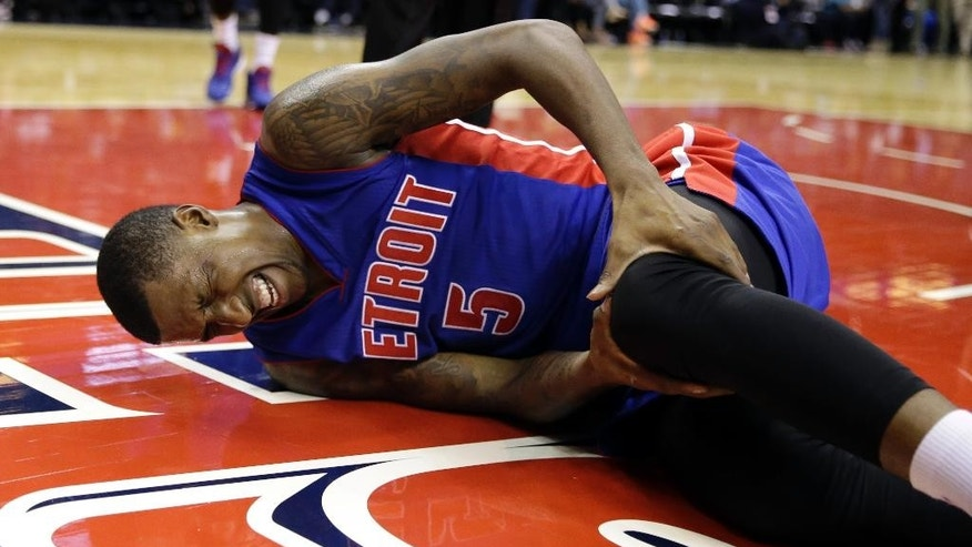 Detroit Pistons guard Kentavious Caldwell-Pope holds his knee after falling in the second half of a preseason NBA basketball game against the Washington Wizards, Sunday, Oct. 12, 2014, in Washington. The Wizards won 91-89. (AP Photo/Alex Brandon)