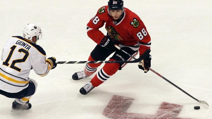 Chicago Blackhawks right wing Patrick Kane (88) controls the puck against Buffalo Sabres right wing Brian Gionta (12) during the third period of an NHL hockey game in Chicago, Saturday, Oct. 11, 2014. The Blackhawks won 6-2. (AP Photo/Nam Y. Huh)