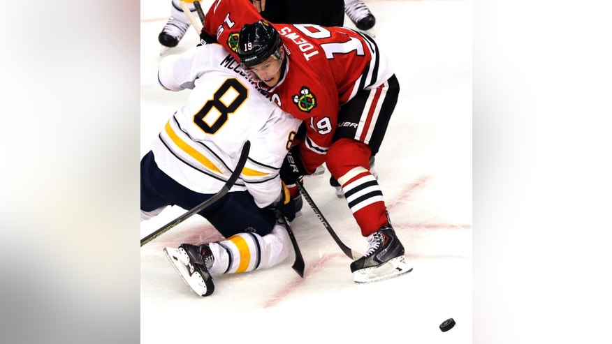 Chicago Blackhawks center Jonathan Toews (19) battles for the puck against Buffalo Sabres center Cody McCormick (8) during the third period of an NHL hockey game in Chicago, Saturday, Oct. 11, 2014. The Blackhawks won 6-2. (AP Photo/Nam Y. Huh)