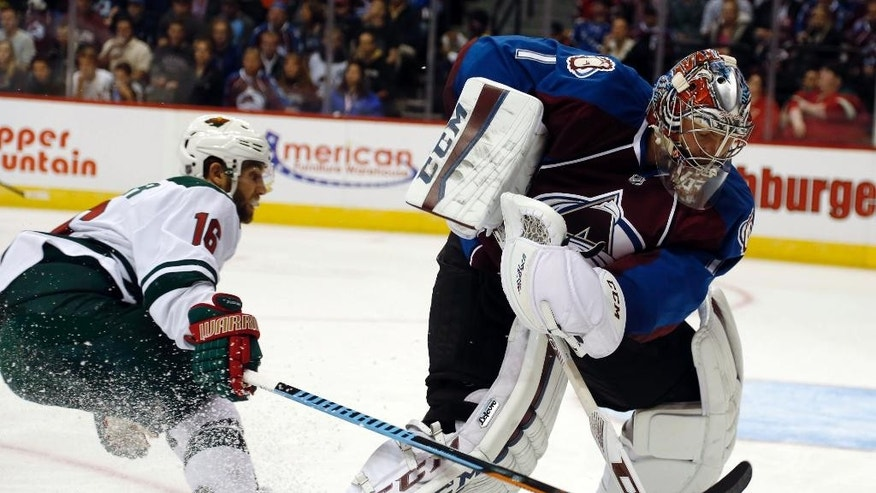 Minnesota Wild left wing Jason Zucker, left, puts a stick on Colorado Avalanche goalie Semyon Varlamov, of Russia, as he clears the puck from beside the net in the first period of a NHL hockey game in Denver on Saturday, Oct. 11, 2014. (AP Photo/David Zalubowski)