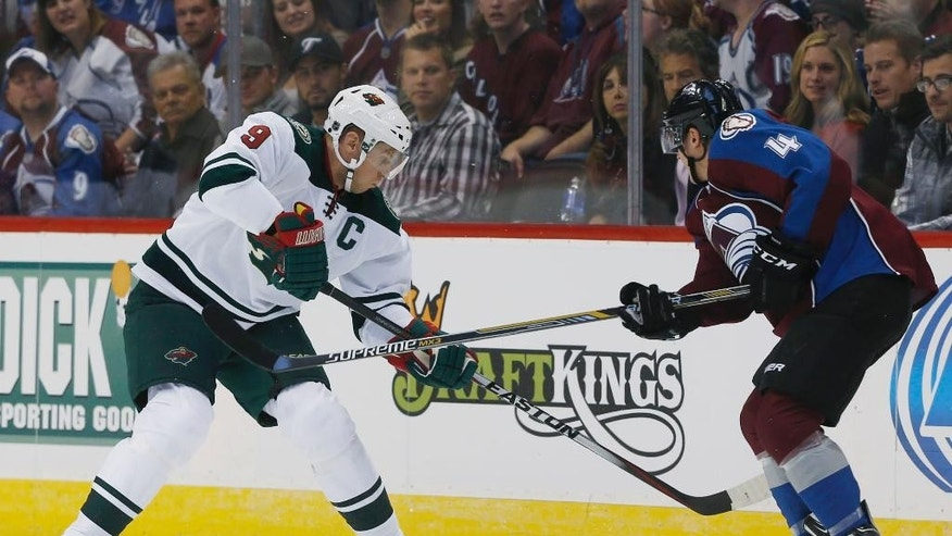 Minnesota Wild center Mikko Koivu, left, of Finland, tries to control the puck as Colorado Avalanche defenseman Tyson Barrie covers in the first period of a hockey game in Denver on Saturday, Oct. 11, 2014. (AP Photo/David Zalubowski)