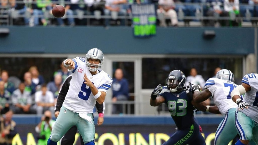 Dallas Cowboys quarterback Tony Romo passes under pressure from Seattle Seahawks defensive end O'Brien Schofield (93) in the second half of an NFL football game, Sunday, Oct. 12, 2014, in Seattle. (AP Photo/Elaine Thompson)
