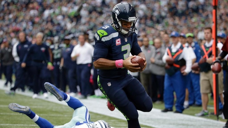 Seattle Seahawks quarterback Russell Wilson (3) runs for a touchdown as Dallas Cowboys strong safety Jeff Heath goes down after missing the tackle in the second half of an NFL football game, Sunday, Oct. 12, 2014, in Seattle. (AP Photo/Elaine Thompson)