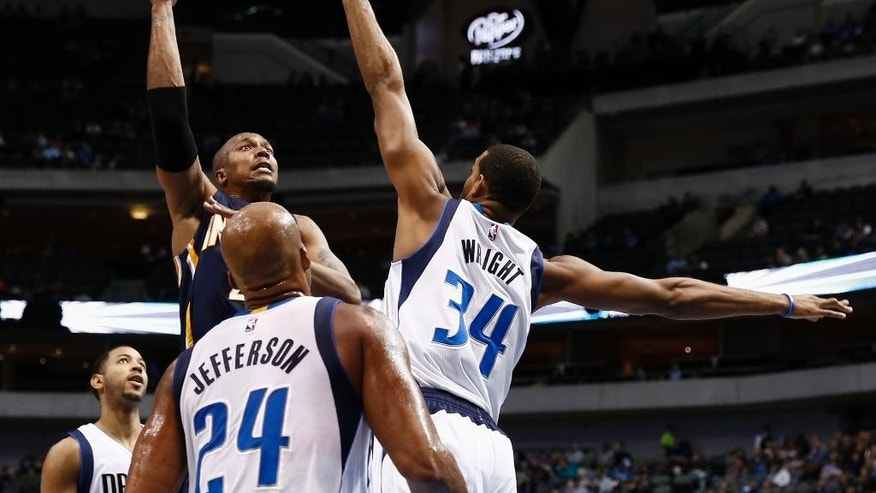 Indiana Pacers forward David West (21) shoots over Dallas Mavericks forward Brandan Wright (34) and forward Richard Jefferson (24) during the first half of a preseason NBA basketball game, Sunday, Oct. 12, 2014, in Dallas, Texas. (AP Photo/Jim Cowsert)