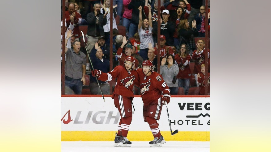With Arizona Coyotes fans cheering in the background, Coyotes' Antoine Vermette, left, celebrates his goal against the Los Angeles Kings with teammate Shane Doan (19) during the first period of an NHL hockey game Saturday, Oct. 11, 2014, in Glendale, Ariz. (AP Photo/Ross D. Franklin)