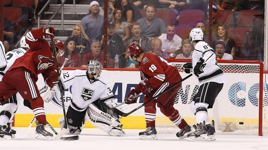 Arizona Coyotes' Antoine Vermette, left, scores a goal against Los Angeles Kings' Jonathan Quick (32) as Kings' Drew Doughty (8) and Coyotes' Shane Doan (19) look on during the first period of an NHL hockey game Saturday, Oct. 11, 2014, in Glendale, Ariz. (AP Photo/Ross D. Franklin)