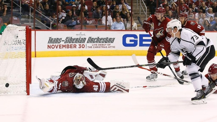 Arizona Coyotes' Devan Dubnyk (40) makes a sprawling save on a shot by Los Angeles Kings' Tyler Toffoli (73) as Coyotes' Joe Vitale (14) and Oliver Ekman-Larsson, of Sweden, look on during the first period of an NHL hockey game Saturday, Oct. 11, 2014, in Glendale, Ariz. (AP Photo/Ross D. Franklin)