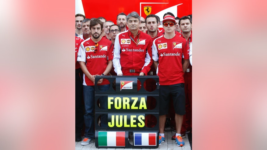 Ferrari driver Fernando Alonso of Spain, left, his teammate  Kimi Raikkonen of Finland, right, and team principal Alberto Mattiacci react after posing for photographers with a banner reading 'Forza Jules' (Go Jules') in the paddock prior to the start of the Formula One Russian Grand Prix at the 'Sochi Autodrom' Formula One circuit, in Sochi, Russia, Sunday, Oct. 12, 2014. The Marussia Formula One team is running only one car at the inaugural Russian Grand Prix this weekend as a sign of respect for injured driver Jules Bianchi. The 25-year-old Bianchi suffered a severe head injury at last Sunday's Japanese Grand Prix in Suzuka and remains in critical condition in a hospital in Japan. (AP Photo/Luca Bruno)