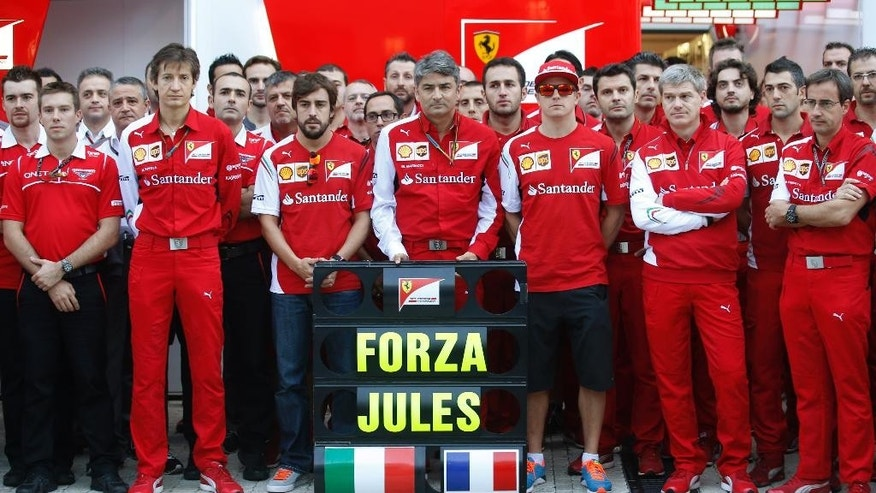 Ferrari driver Fernando Alonso of Spain, center left, his teammate  Kimi Raikkonen of Finland, center right, and team principal Alberto Mattiacci react after posing for photographers with a banner reading 'Forza Jules' (Go Jules') in the paddock prior to the start of the Formula One Russian Grand Prix at the 'Sochi Autodrom' Formula One circuit, in Sochi, Russia, Sunday, Oct. 12, 2014. The Marussia Formula One team is running only one car at the inaugural Russian Grand Prix this weekend as a sign of respect for injured driver Jules Bianchi. The 25-year-old Bianchi suffered a severe head injury at last Sunday's Japanese Grand Prix in Suzuka and remains in critical condition in a hospital in Japan. (AP Photo/Luca Bruno)