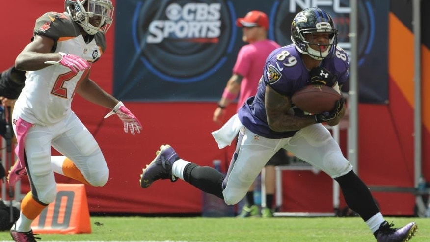 Baltimore Ravens wide receiver Steve Smith (89) catches a 56-yard touchdown pass in front of Tampa Bay Buccaneers cornerback Alterraun Verner (21) during the first half of an NFL football game in Tampa, Fla., Sunday, Oct. 12, 2014. (AP Photo/Steve Nesius)