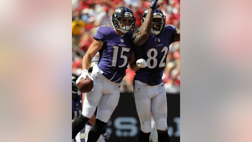 Baltimore Ravens wide receiver Michael Campanaro (15) and wide receiver Torrey Smith (82) celebrate after Campanaro caught a 19-yard pass for a touchdown against the Tampa Bay Buccaneers during the first half of an NFL football game in Tampa, Fla., Sunday, Oct. 12, 2014. (AP Photo/Steve Nesius)