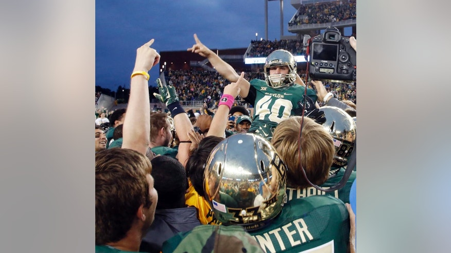 Baylor place kicker Chris Callahan (40) is lifted up by the team after connecting for the game-winning field goal against TCU in the second half of an NCAA college football game, Saturday, Oct. 11, 2014, in Waco, Texas. Baylor won 61-58. (AP Photo/Waco Tribune Herald, Rod Aydelotte)