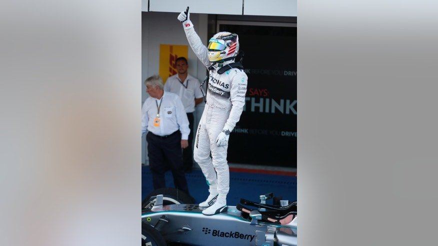 Mercedes driver Lewis Hamilton of Britain celebrates standing on his car after winning the Formula One Russian Grand Prix at the 'Sochi Autodrom' Formula One circuit, in Sochi, Russia, Sunday, Oct. 12, 2014. (AP Photo/Luca Bruno)