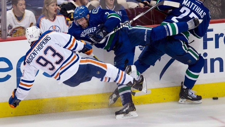 Vancouver Canucks defenceman Dan Hamhuis (2) goes into the boards as he hits Edmonton Oilers center Ryan Nugent-Hopkins (93) as Canucks center Shawn Matthias (27) looks for the puck during the third period of NHL action in Vancouver, British Columbia Saturday, Oct. 11, 2014. (AP Photo/The Canadian Press, Jonathan Hayward)