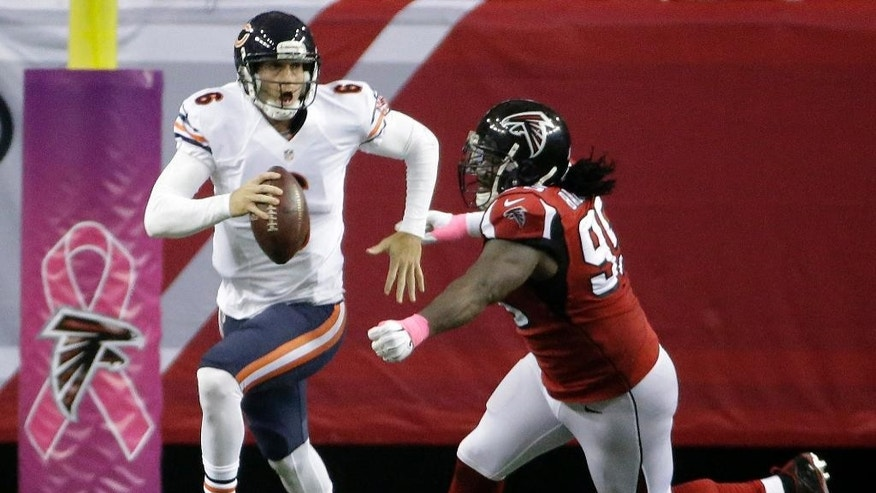Chicago Bears quarterback Jay Cutler (6) runs from Atlanta Falcons defensive end Jonathan Babineaux (95) during the second half of an NFL football game, Sunday, Oct. 12, 2014, in Atlanta. (AP Photo/David Goldman)