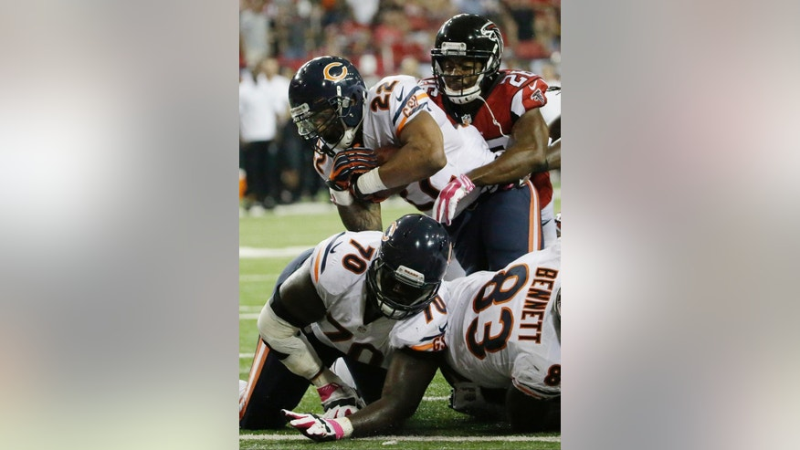 Chicago Bears running back Matt Forte (22) scores a touchdown against Atlanta Falcons cornerback Josh Wilson (26) during the second half of an NFL football game, Sunday, Oct. 12, 2014, in Atlanta. (AP Photo/David Goldman)