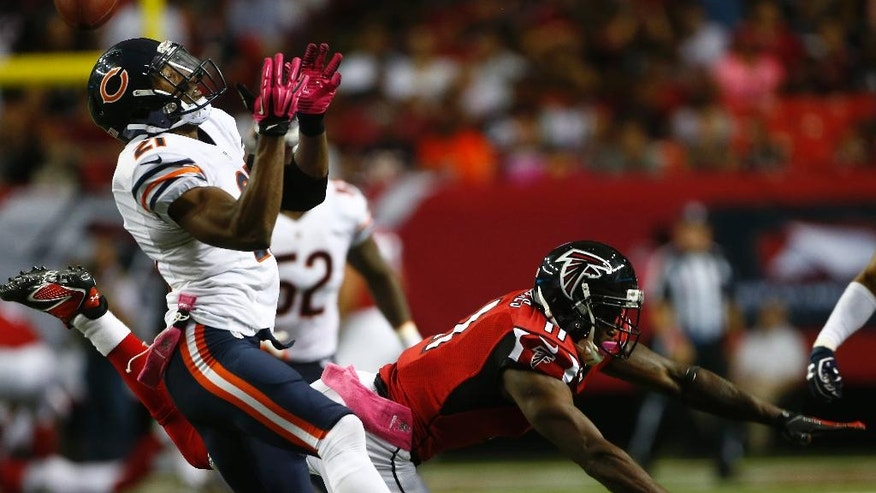 Atlanta Falcons wide receiver Julio Jones (11) falls away as Chicago Bears strong safety Ryan Mundy (21) vies for the loose ball during the second half of an NFL football game, Sunday, Oct. 12, 2014, in Atlanta. (AP Photo/John Bazemore)