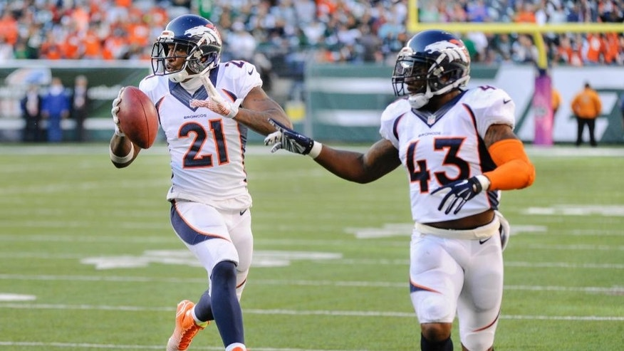 Denver Broncos cornerback Aqib Talib (21) runs into the end zone for a touchdown as strong safety T.J. Ward (43) blocks after intercepting a pass against the New York Jets during the fourth quarter of an NFL football game, Sunday, Oct. 12, 2014, in East Rutherford, N.J. The Broncos won 31-17. (AP Photo/Bill Kostroun)