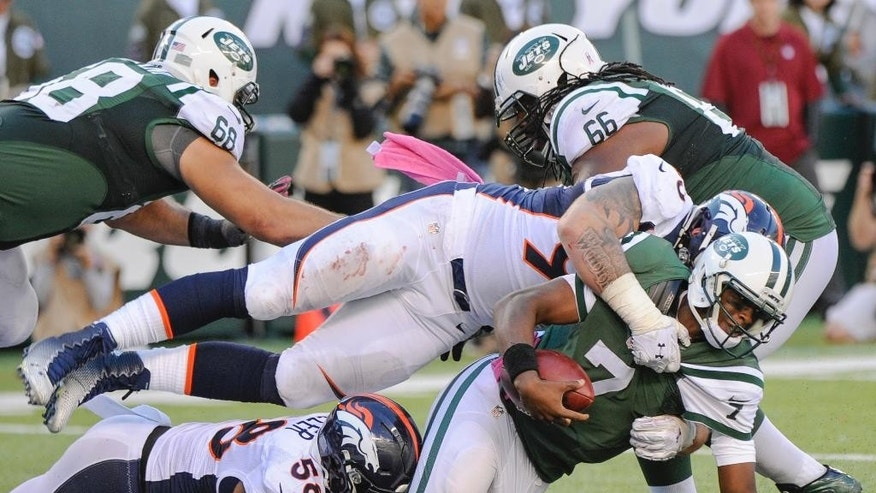New York Jets quarterback Geno Smith (7) is sacked by Denver Broncos outside linebacker Von Miller (58) and defensive end Derek Wolfe (95) as he scrambles out of the end zone during the fourth quarter of an NFL football game, Sunday, Oct. 12, 2014, in East Rutherford, N.J. The Broncos won 31-17. (AP Photo/Bill Kostroun)