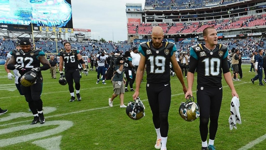 Jacksonville Jaguars kicker Josh Scobee (10) and punter Bryan Anger (19) leave the field after the Jaguars lost to the Tennessee Titans 16-14 in an NFL football game Sunday, Oct. 12, 2014, in Nashville, Tenn. A 55-yard field goal attempt by Scobee in the final seconds of the game was blocked. (AP Photo/Mark Zaleski)