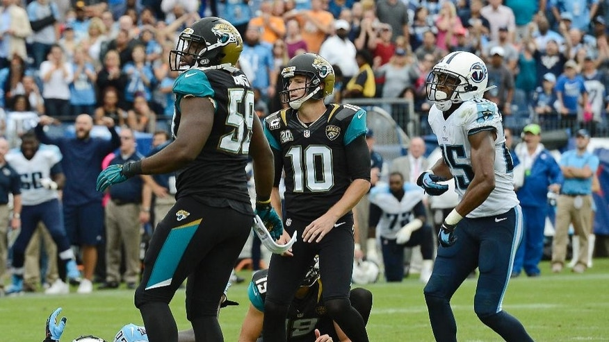 Jacksonville Jaguars kicker Josh Scobee (10), defensive end Ryan Davis (59), and Tennessee Titans cornerback Blidi Wreh-Wilson (25) watch Scobee's 55-yard field goal attempt in the final seconds of the fourth quarter of an NFL football game Sunday, Oct. 12, 2014, in Nashville, Tenn. The Titans blocked the kick to preserve a 16-14 win for the Titans. (AP Photo/Mark Zaleski)