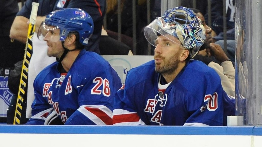 New York Rangers goalie Henrik Lundqvist (30) sits on the bench next to Martin St. Louis (26) after being taken out of the game after Toronto Maple Leafs' David Clarkson scored in the second period of an NHL hockey game at Madison Square Garden on Sunday, Oct. 12, 2014, in New York. (AP Photo/Kathy Kmonicek)