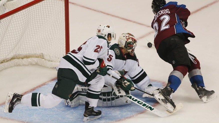 Colorado Avalanche left wing Gabriel Landeskog, right, of Sweden, flies past Minnesota Wild goalie Darcy Kuemper, center, as he stops shot while defenseman Jonas Brodin covers in the third period of the Wild's 3-0 victory in an NHL hockey game in Denver on Saturday, Oct. 11, 2014. (AP Photo/David Zalubowski)