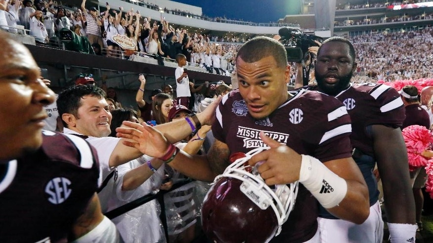 Mississippi State quarterback Dak Prescott, center, celebrates with teammates as they leave Scott Field following their 38-23 win over No. 2 Auburn in an NCAA college football game in Starkville, Miss., Saturday, Oct 11, 2014.  (AP Photo/Rogelio V. Solis)