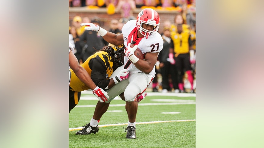 Georgia's Nick Chubb, right, tries to spin out of the hands of Missouri's Markus Golden, left, during the first quarter of an NCAA college football game Saturday, Oct. 11, 2014, in Columbia, Mo. (AP Photo/L.G. Patterson)