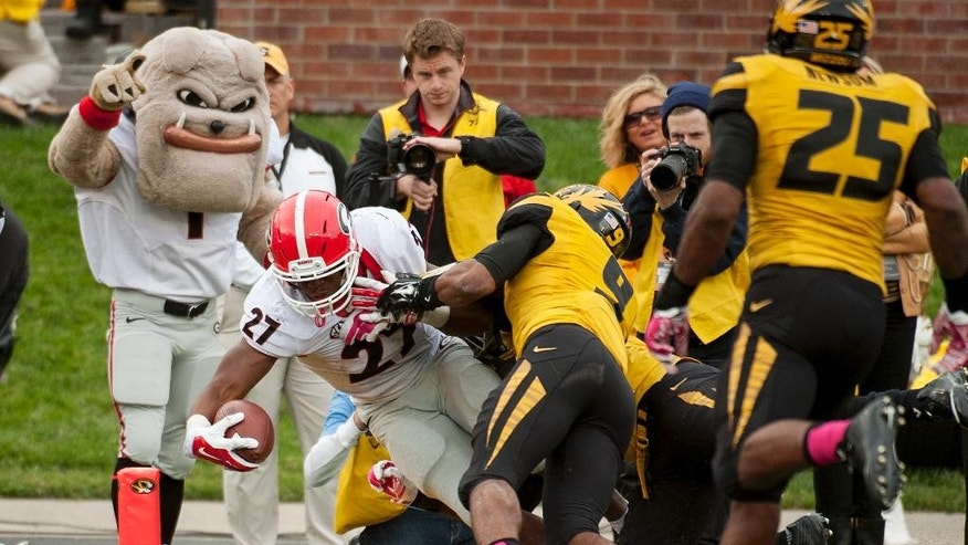 Georgia running back Nick Chubb, left, scores a touchdown as he gets past Missouri's Braylon Webb, center, and Donavin Newsom, right, during the fourth quarter of an NCAA college football game Saturday, Oct. 11, 2014, in Columbia, Mo. Georgia won the game 34-0. (AP Photo/L.G. Patterson)