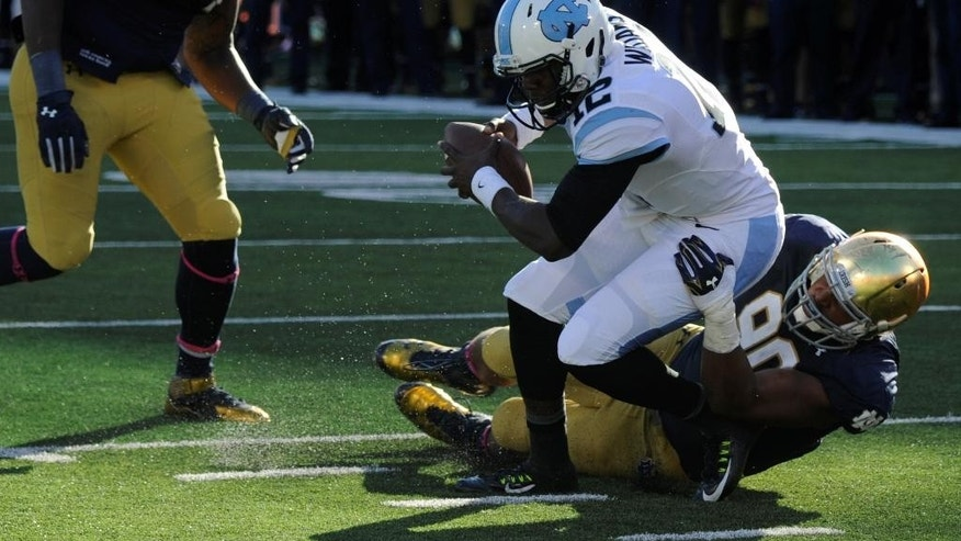 North Carolina quarterback Marquise Williams is tackled at the 3-yard line by Notre Dame defensive lineman Issac Rochell but ends up in the end zone as Notre Dame's Jarron Jones, left, pursues in the first half of an NCAA college football game, Saturday, Oct. 11, 2014, in South Bend, Ind. (AP Photo/Joe Raymond)