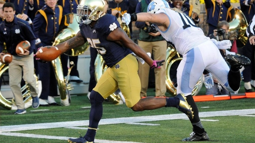 Notre Dame running back Taraen Folston, left, scores a touchdown as North Carolina Jeff Schoettmer gives chase in the second half of an NCAA college football game Saturday, Oct. 11, 2014, in South Bend, Ind. (AP Photo/Joe Raymond)