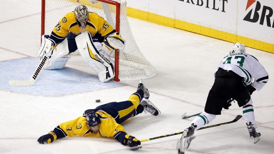 Nashville Predators defenseman Seth Jones (3) sprawls on the ice as he tries to block a shot by Dallas Stars right wing Valeri Nichushkin (43), of Russia, in the second period of an NHL hockey game Saturday, Oct. 11, 2014, in Nashville, Tenn. Predators goalie Pekka Rinne (35), of Finland, watches the action. (AP Photo/Mark Humphrey)