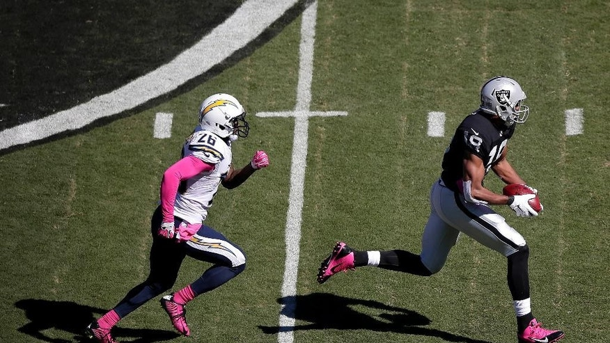 Oakland Raiders wide receiver Andre Holmes, right, runs past San Diego Chargers defensive back Brandon Flowers to score on a 77-yard touchdown pass during the first quarter of an NFL football game in Oakland, Calif., Sunday, Oct. 12, 2014.  (AP Photo/Marcio Jose Sanchez)