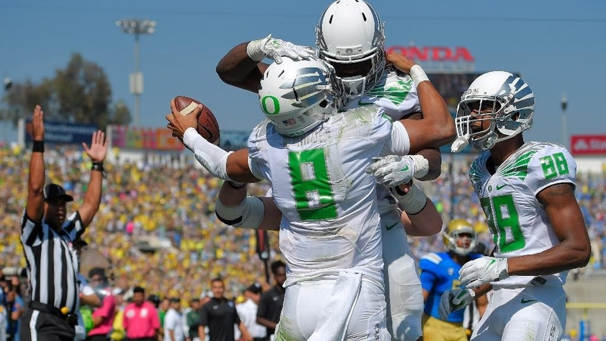 Oregon quarterback Marcus Mariota, second from left, celebrates his touchdown with running back Royce Freeman, second from right, as wide receiver Dwayne Stanford, right, looks on and an official signals during the first half of a NCAA college football game against UCLA, Saturday, Oct. 11, 2014, in Pasadena, Calif. (AP Photo/Mark J. Terrill)