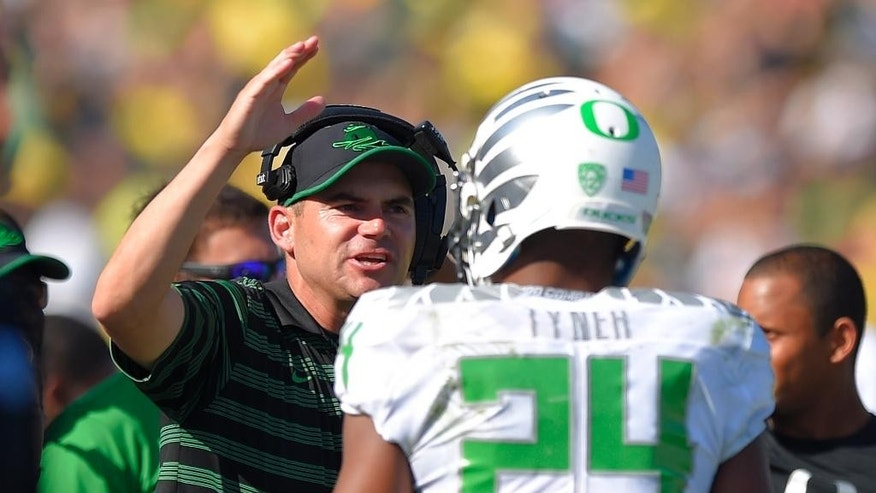 Oregon head coach Mark Helfrich, left, congratulates running back Thomas Tyner after the team scored a touchdown during the second half of a NCAA college football game against UCLA, Saturday, Oct. 11, 2014, in Pasadena, Calif. Oregon won 42-30. (AP Photo/Mark J. Terrill)
