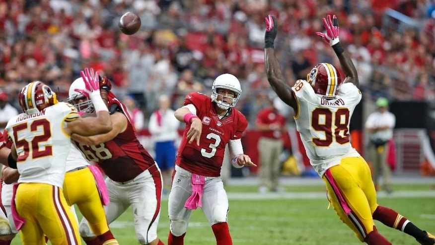 Arizona Cardinals quarterback Carson Palmer (3) throws as Washington Redskins outside linebacker Brian Orakpo (98) pursues during the first half of an NFL football game, Sunday, Oct. 12, 2014, in Glendale, Ariz. (AP Photo/Rick Scuteri)