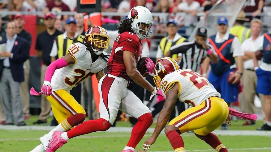 Arizona Cardinals wide receiver Larry Fitzgerald (11) runs in a touchdown after a catch as Washington Redskins free safety E.J. Biggers (30) and Ryan Clark (25) pursue during the first half of an NFL football game, Sunday, Oct. 12, 2014, in Glendale, Ariz. (AP Photo/Rick Scuteri)