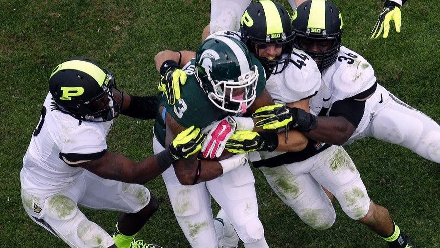 Michigan State running back Jeremy Langford (33) gets tackled by a gang of Purdue defenders during the second half of an NCAA college football game in West Lafayette, Ind., Saturday, Oct. 11, 2014. Michigan State won 45-31. (AP Photo/AJ Mast)