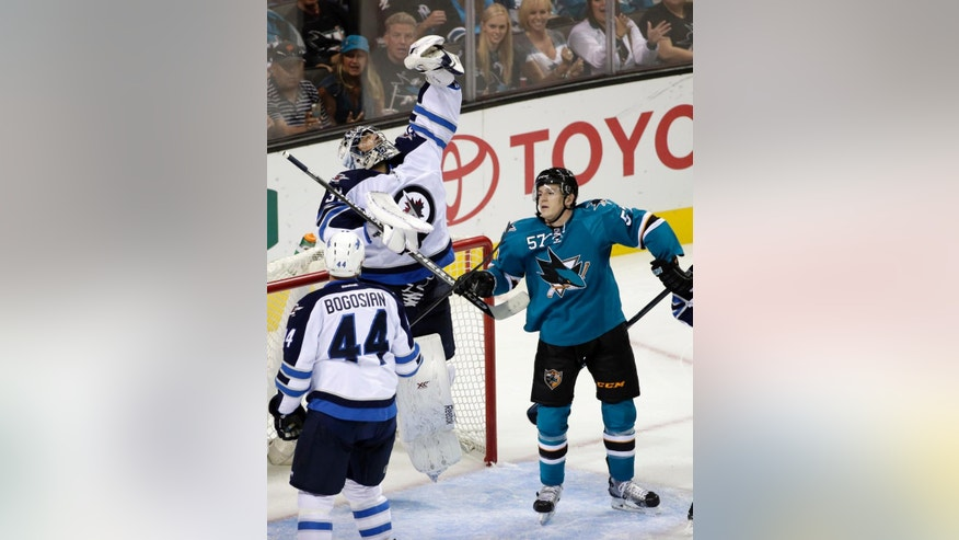 Winnipeg Jets goalie Ondrej Pavelec, of the Czech Republic, leaps to make a save next to San Jose Sharks center Tommy Wingels (57) during the second period of an NHL  hockey game Saturday, Oct. 11, 2014, in San Jose, Calif. (AP Photo/Marcio Jose Sanchez)