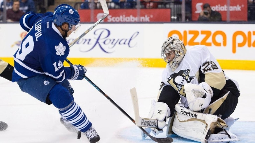 Pittsburgh Penguins goaltender Marc-Andre Fleury makes a save on Toronto Maple Leafs Joffrey Lupul during the second period of an NHL hockey game, Saturday, Oct. 11, 2014 in Toronto. (AP Photo/The Canadian Press, Frank Gunn)